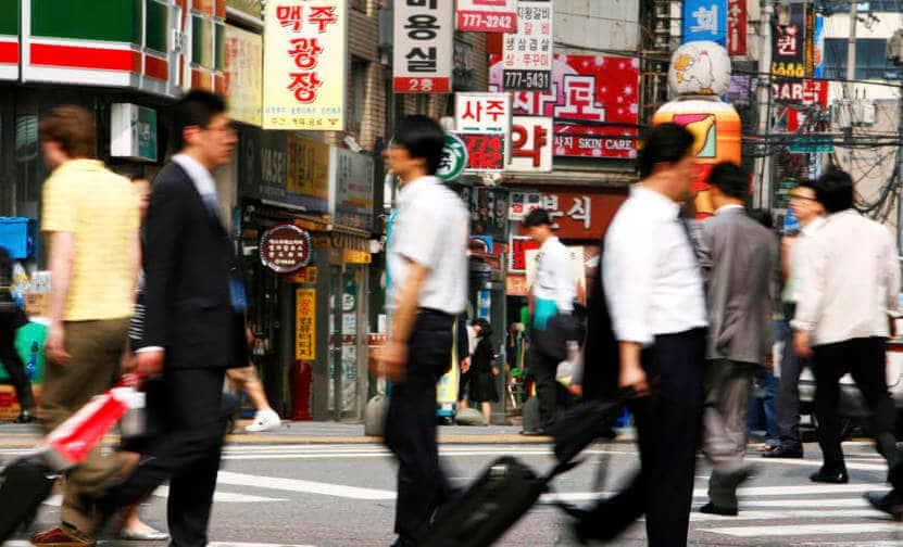 אנשי עסקים מתהלכים ברחובות סיאול בירת דרום קוריאה